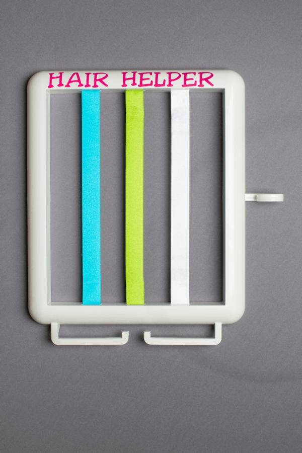 The Hair Helper featuring pink lettering and blue, lime and white ribbons