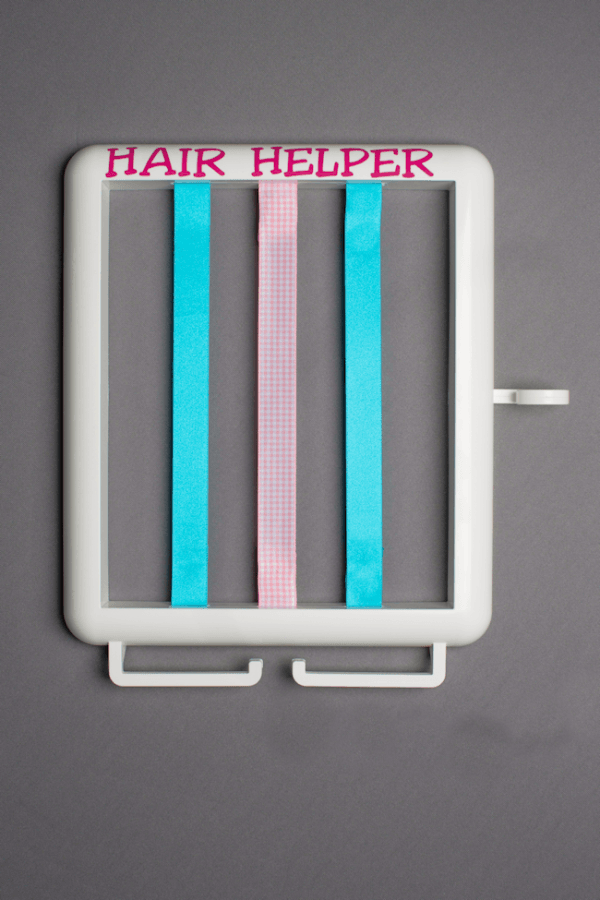 The Hair Helper featuring pink lettering and blue and pink ribbons