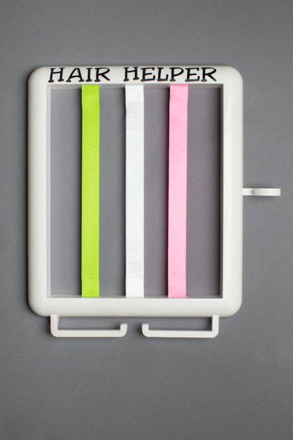 The Hair Helper featuring black lettering and lime, white and pink ribbons