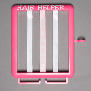 Pink Hair Helper with white stickers and white and pink ribbons on grey background